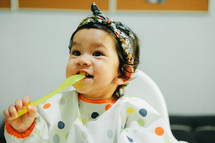 infant girl eating in a high chair