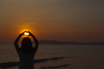a woman holding up her hands in the shape of a heart