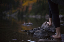 a woman standing on a lake shore in fall barefoot