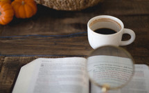 magnifying glass over the pages of a Bible, coffee mug, and pumpkins