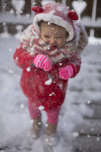 a toddler girl playing in snow but doesn't like it