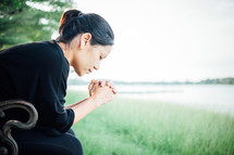 a woman with head bowed and praying hands