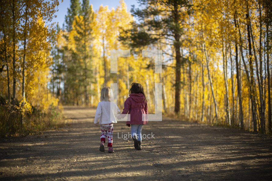 children walking outdoors on a dirt road in fall