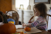 child painting a pumpkin