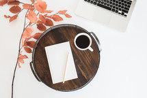 wooden tray, fall foliage, journal, pencil, coffee mug, and laptop on a desk