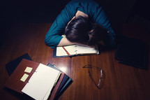 an exhausted woman with her head on her desk