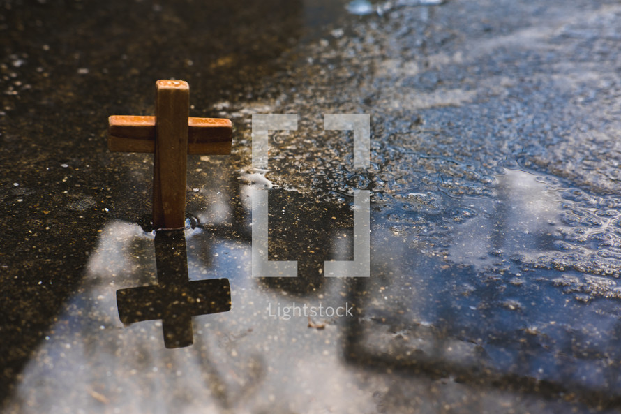 a wooden cross in a puddle