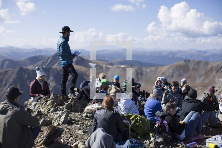 group resting on a mountaintop