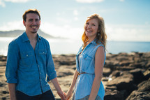 Smiling couple holding hands while standing on the ocean shore outside.