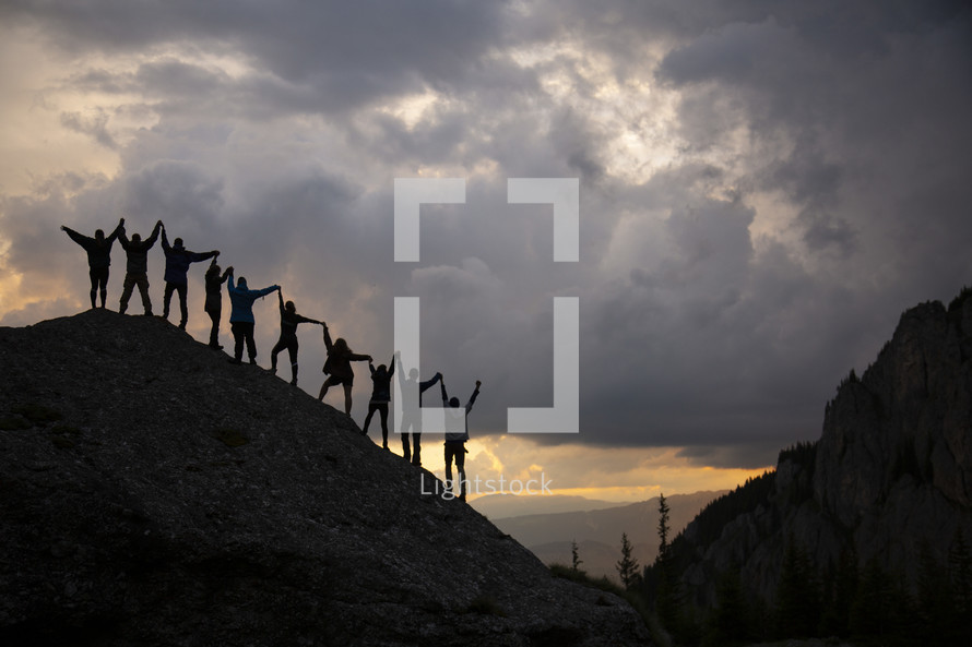 people holding hands standing on a mountainside