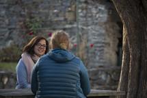 two women talking and praying outdoors