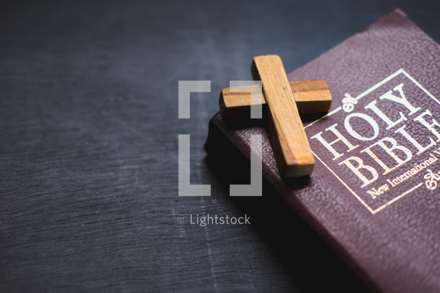 small wooden cross on the cover of a Bible