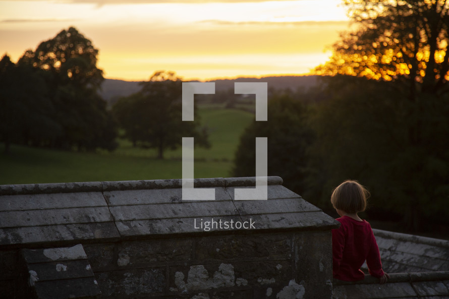 child sitting on a stone wall looking out at a green pasture