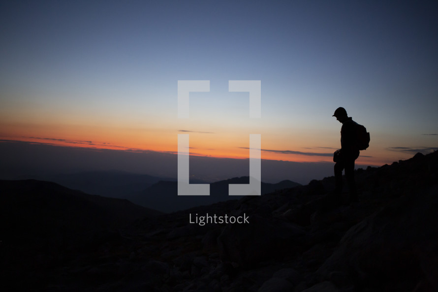 silhouette of a man on a mountaintop at dawn