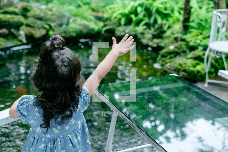 a little girl feeding fish in a koi pond