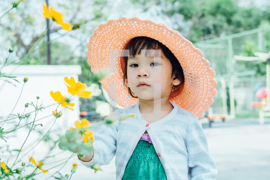 a little girl in a straw hat standing next to flower