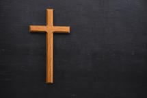wood cross on black background