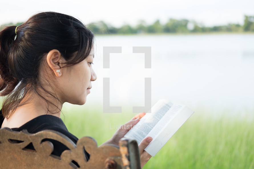 a woman reading a Bible sitting on a park bench