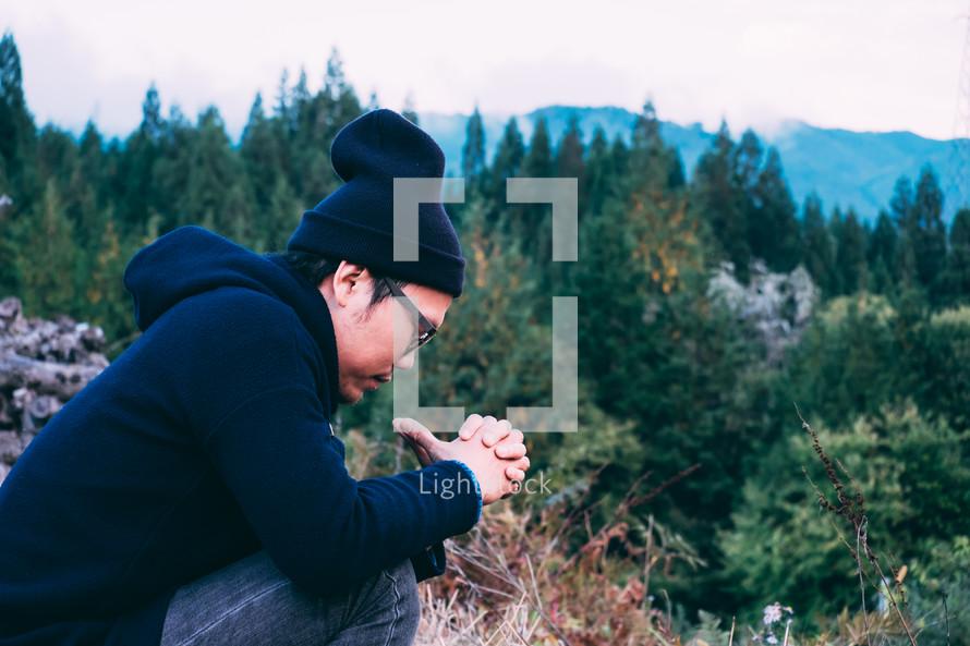 a man praying outdoors