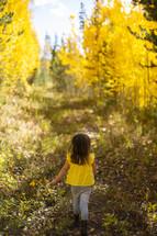 little girl walking under golden fall foliage