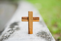 small wooden cross on a railing