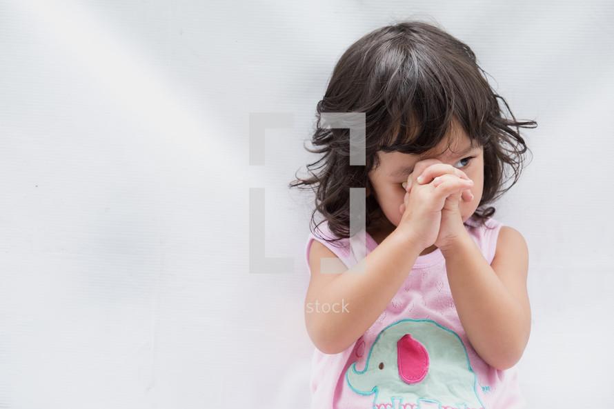 a toddler girl praying