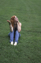 "Teen girl sitting in green grass, looking to heaven, asking ""why?"""
