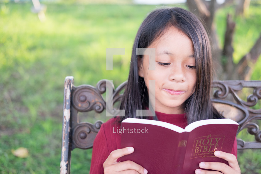 a girl reading a Bible sitting on a park bench