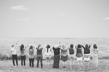 Women holding hands with arms raised in praise while standing in a field.