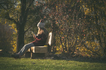 a teen girl sitting on a bench outdoors reading a Bible