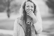 teenage girl laughing with her hand covering her mouth.