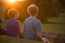 kids sitting outdoors in a green pasture
