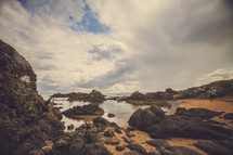 Rocky ocean shoreline under a cloudy sky.
