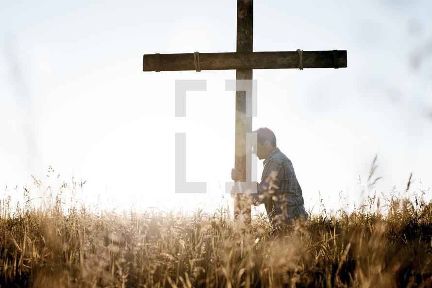 a man standing next to a cross praying