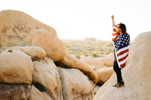 a woman standing in a desert wrapped in an American flag