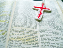 A well read bible is open with a red cross needle point bookmark and highlighted bible verses during quiet time bible study and reading God's word.