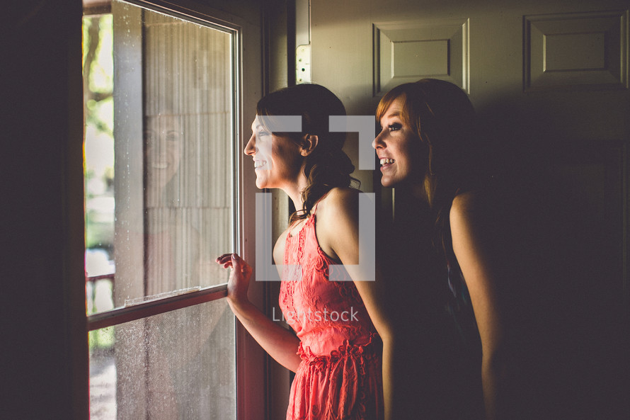 Women looking out a window in excitement.