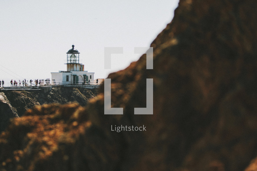 A lighthouse beyond a rocky cliff.