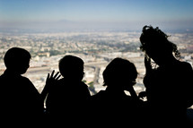 silhouettes of children looking out a window