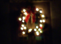 A Christmas Reef decorated with a red bow and white Christmas lights hanging on a door illuminates the darkness from a distance warming the night air with light and feelings of good cheer at Christmastime.