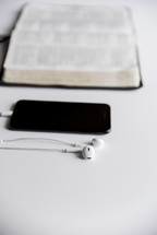 phone, earbuds, and opened Bible
