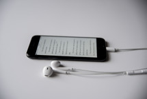 earbuds and Bible app on a cellphone screen