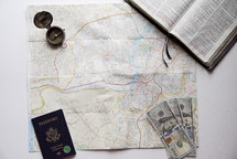 map, passport, Bible and cash on a white background