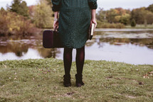 a woman with a suitcase and Bible
