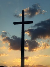 Silhouetted cross reaching out into the sky against a golden yellow sunset.
