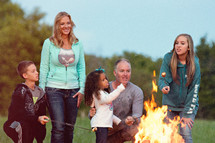 a family standing by a camp fire roasting marshmallows