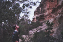 a man looking up to the top of a cliff