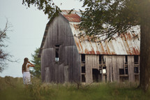 woman and an old weathered barn