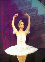 A ballet dancer from the Ukraine wearing white dances on stage surrounded by purple light for a Christmas production of The Nutcracker ballet performance.