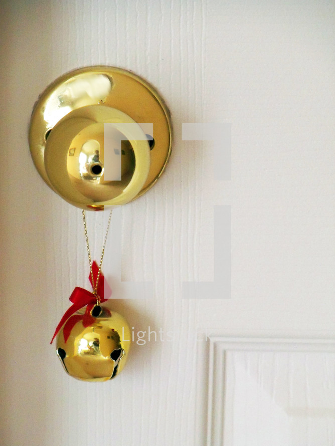 A brass Jingle Bell with a red bow adorns a brass door knob against a white background adding color, warmth and the feelings of the holidays, snow and Christmas warmth and cheer to an otherwise ordinary door entrance allowing the bell to jingle every time the door is opened to help announce visitors and guests coming in for the holidays.